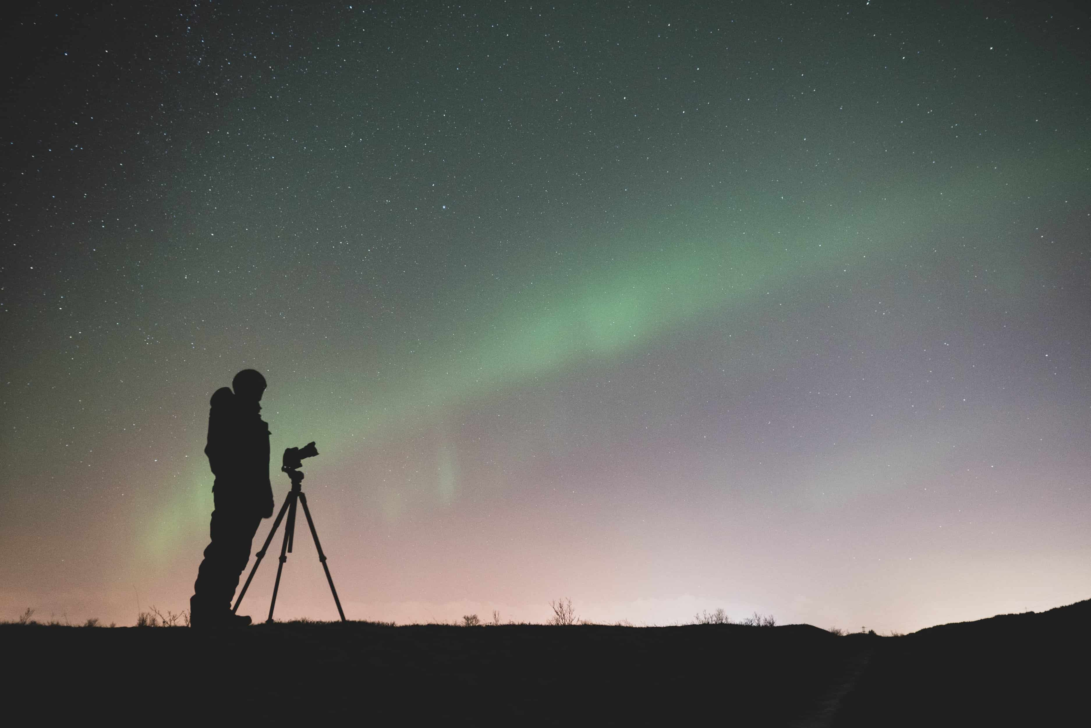 Man Photographing the Northern Lights with his Tripod in South Iceland