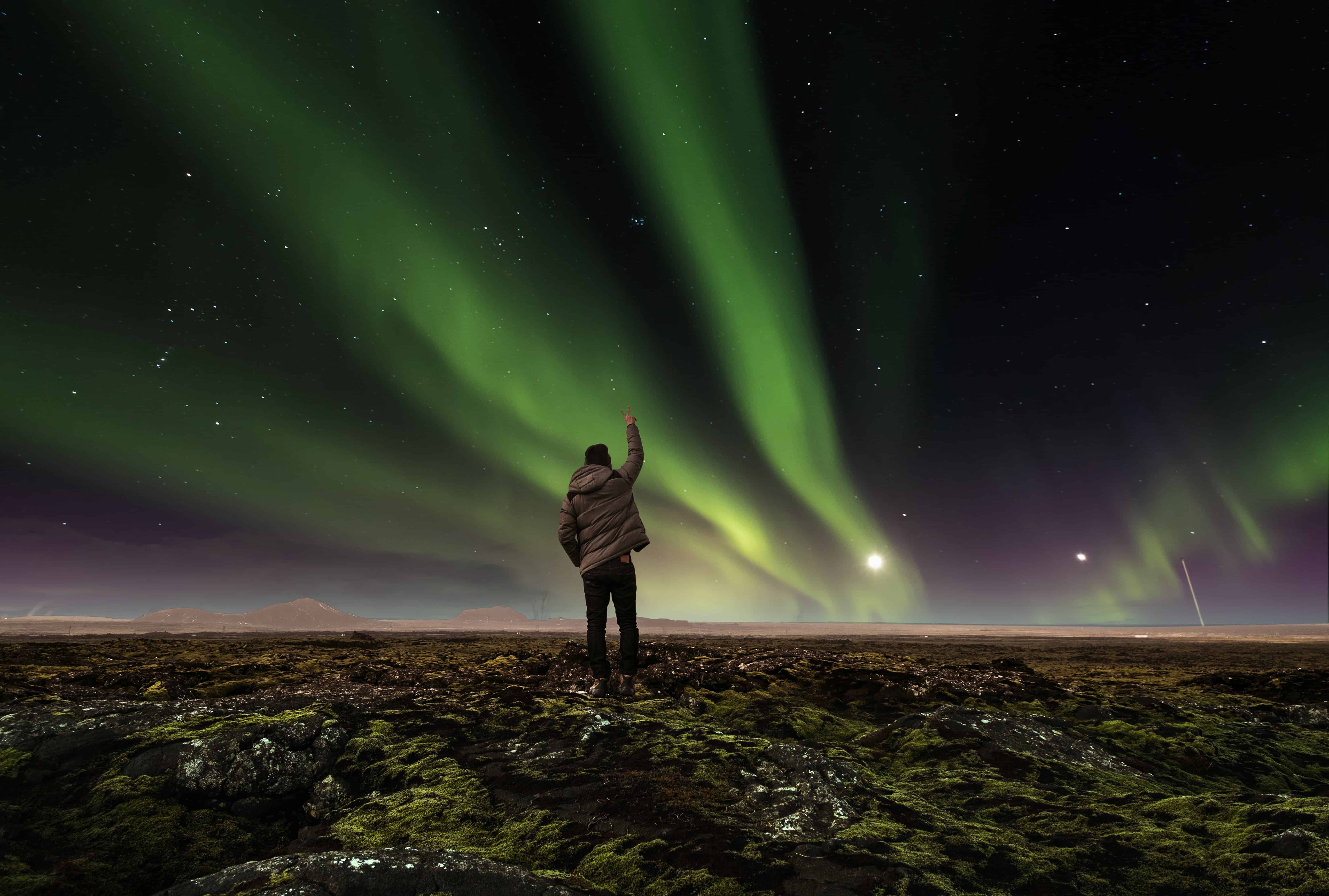 Man in a Lava Field in Iceland Raising His Arm to the Sky With Dancing Northern Lights