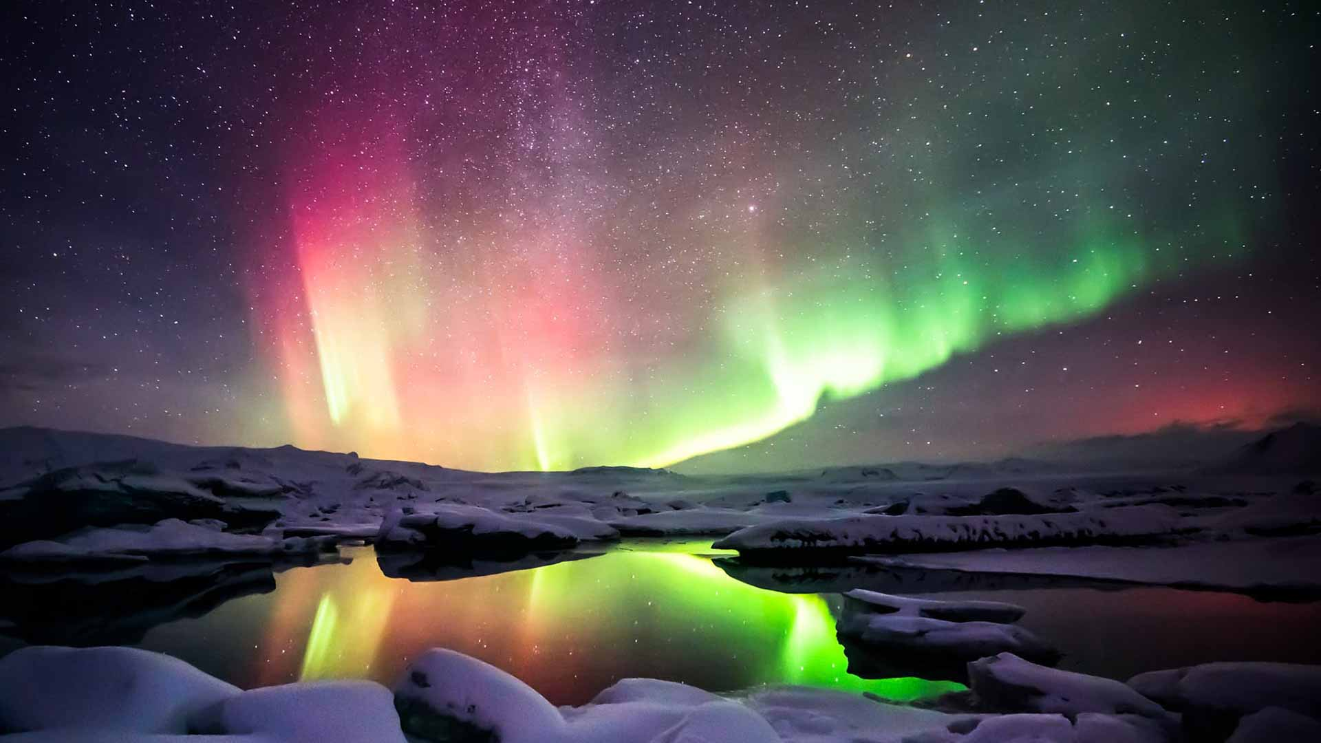 Colorful Northern Lights Dancing Over a Lake With Snow Covered Rocks in Iceland
