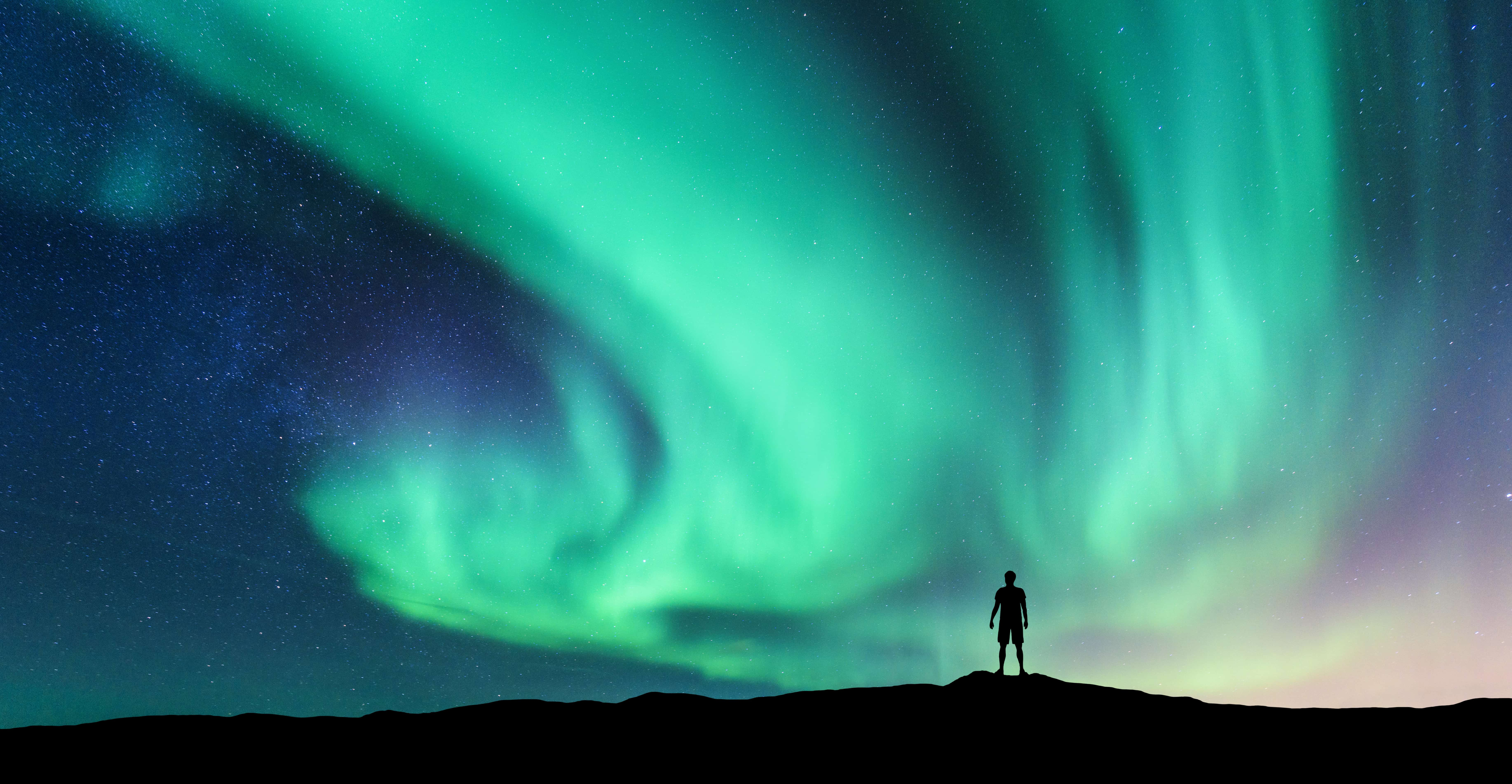 Silhouette of a Man Staring at Dancing Northern Lights