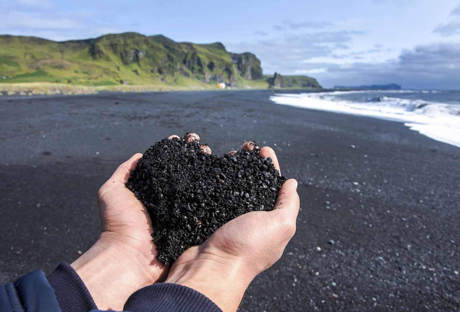 Man Holding Heart Shaped Black Sand on Reynisfjara Black Beach in South Iceland