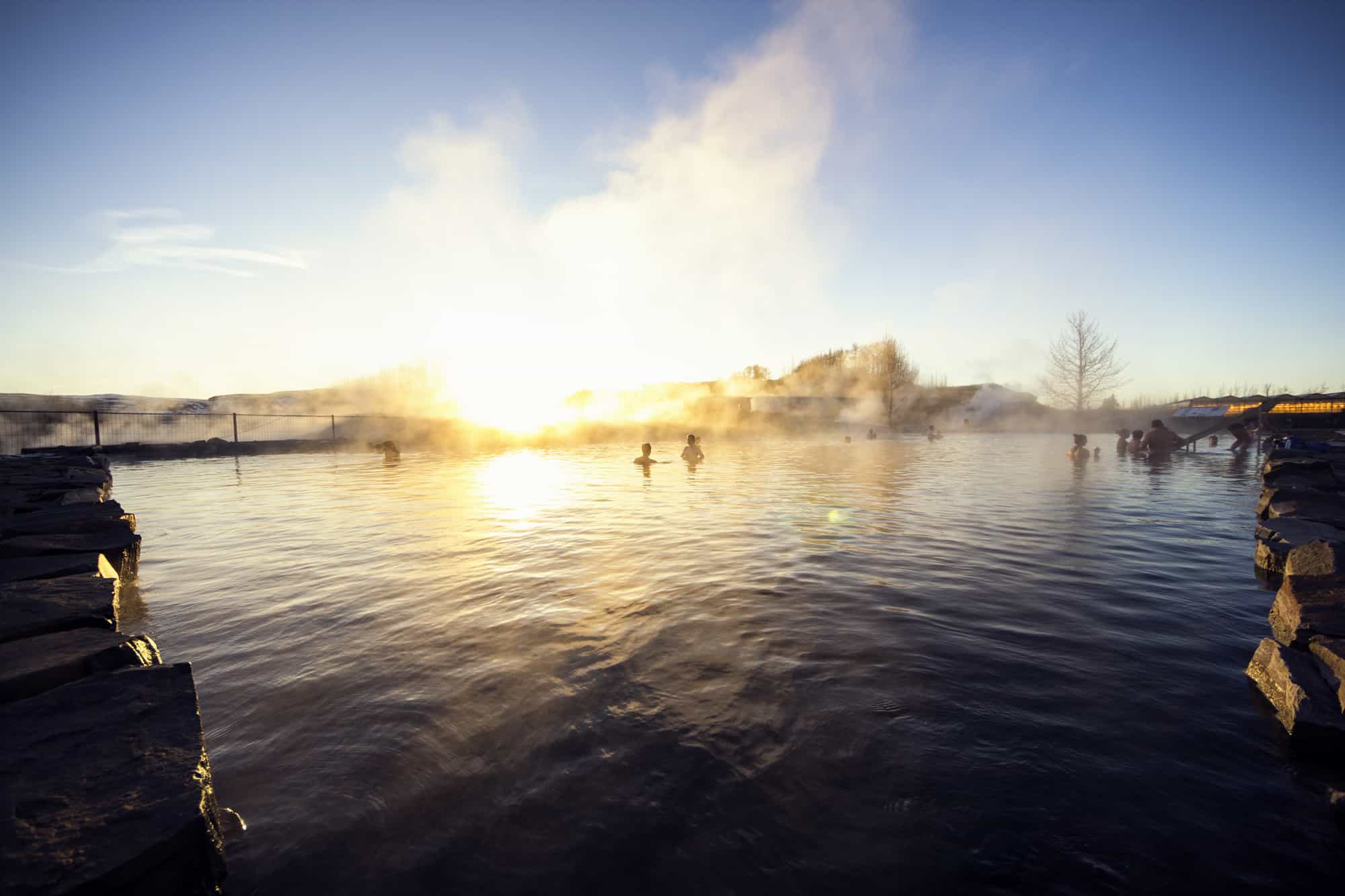 People Bathing in the Secret Lagoon During Winter Sunset in Fludir Iceland